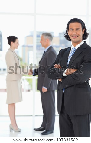 Young executive standing upright in front of business people shaking hands