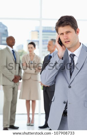 Young executive using a cell phone while his team is behind him
