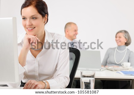 Young executive woman work on computer in office with colleagues