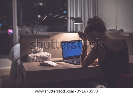 Young exhausted,depressed,concentrated woman sitting in her room or office with french windows in the dark.Studies late at night.Staying up late. Overworking.Feeling under pressure and headache