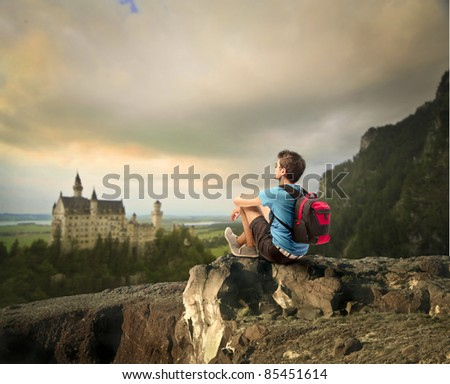 Young explorer sitting on a rock in front of a fairy tale castle