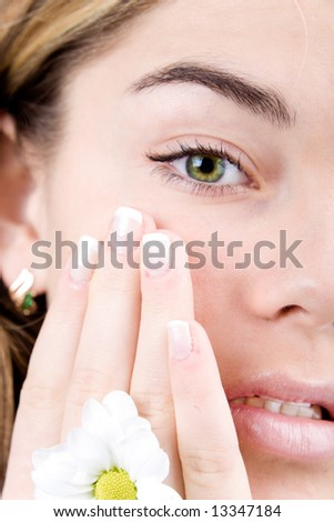 Young face with green eyes and nails french close-up with daisy