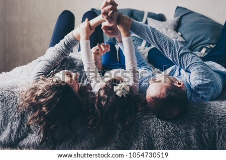 Young family are lying on bed and playing with their hands. Mom, dad and little daughter. People are enjoying their company. Childhood and parenthood. Happiness. Happy moments. Casual lifestyle.  #1054730519