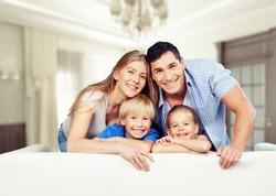 Young  family at home smiling at camera