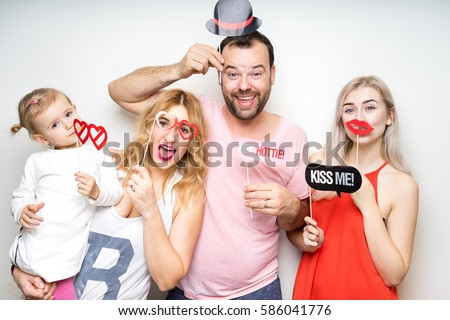 young family at white background photo booth with party props happy funny smile strike pose celebration wedding anniversary  #586041776