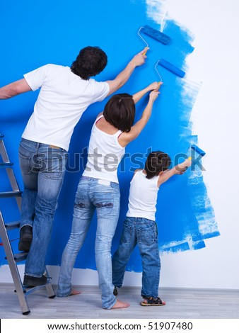 Young family brushing the wall together into the blue color