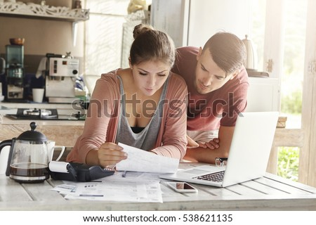 Young family calculating domestic finances together at home. Woman reading information in piece of paper with serious concentrated look while paying utility bills online using laptop in kitchen