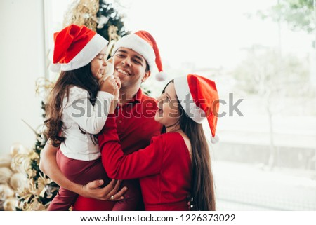 Young family celebrating Christmas at home.Happy young family enjoying their holiday time together. #1226373022