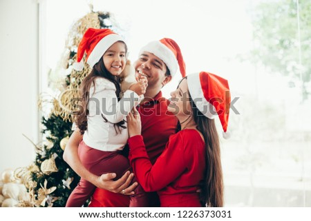 Young family celebrating Christmas at home.Happy young family enjoying their holiday time together. #1226373031