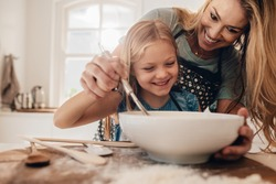 Young family cooking food in kitchen. Happy young girl with her mother mixing batter in the bowl.