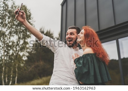 Young family couple have fun and taking selfie in front of their house. Bearded man and redhead woman bought a house and taking emotion selfie on phone in front of their house. Stay at home concept Stock foto ©