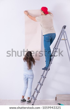 Young family doing renovation at home with new wallpaper