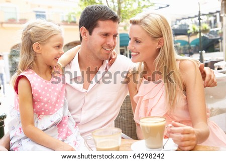 Young Family Enjoying Cup Of Coffee In Cafe Together
