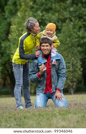 Young Family father, mother and child pose in park by autumn