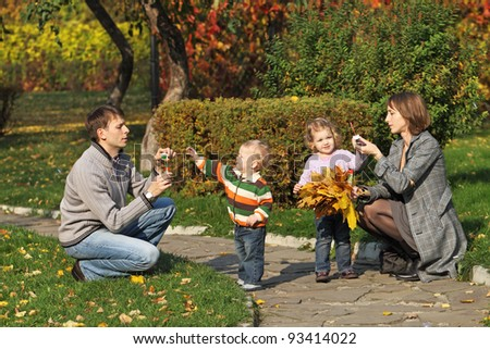 Young family for a walk in the autumn park with two children bubbles