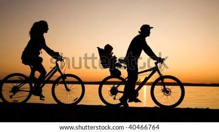 Young family go for a cycle ride on the beach at background sunset