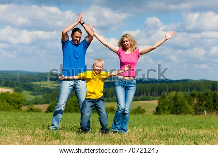 Young family having a walk in the sun over the meadow on a bright summer day
