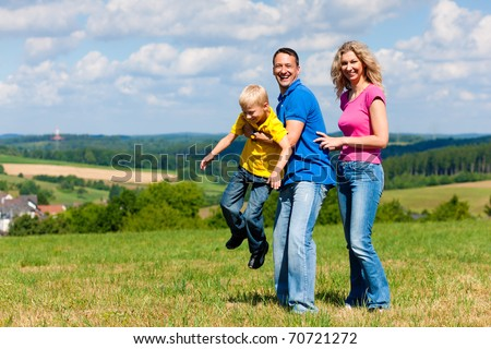 Young family having a walk in the sun over the meadow on a bright summer day and making jokes