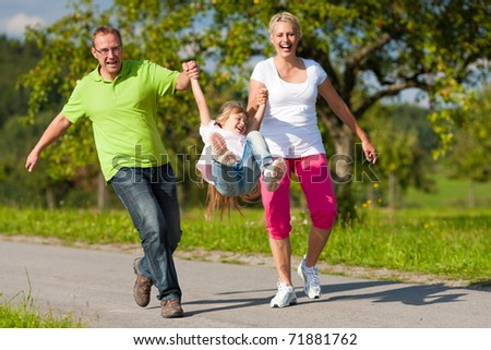 Young family having a walk running on a path and letting the kid fly high