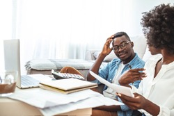 Young family having debt problems, not able to pay out their loan. Male in glasses and curlu woman studying paper form bank while managing domestic budget together in livingroom interior