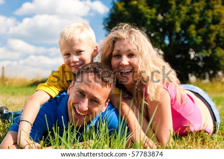 Young family having fun in the sun lying on the meadow an a bright summer day