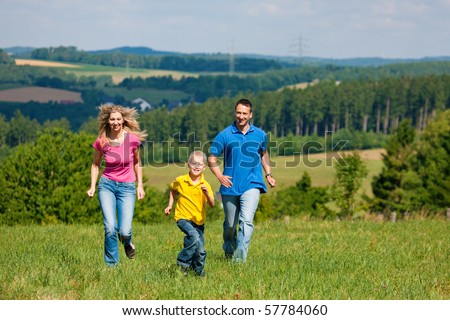 Young family having fun in the sun running over the meadow an a bright summer day