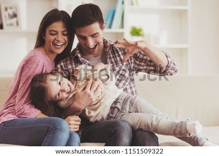 Young Family Having Fun. Together at Home. Happy Childhood. Attractive Young Couple. Parents and Kid Sitting on Sofa. Portrait at Home. Family Concept. Smiling Parents. Child at Home.