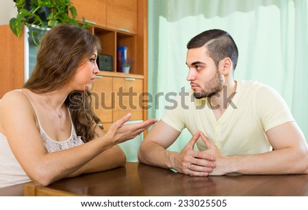 Young family having serious talking at the table in home #233025505