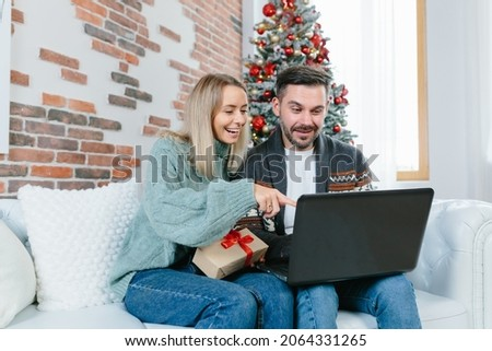 Young family husband and wife choose together Christmas gifts in an online store, sitting at home near the Christmas tree with a laptop