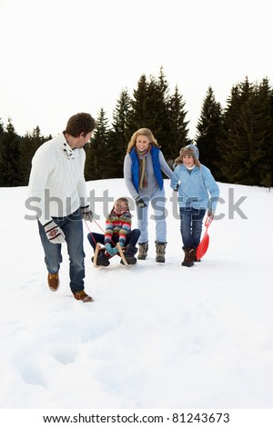 Young Family In Alpine Snow Scene With Sled - stock photo