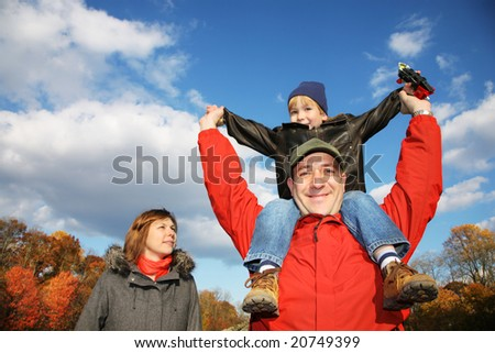 Young family in autumn park. Father holding his son on his shoulders against blue sky.