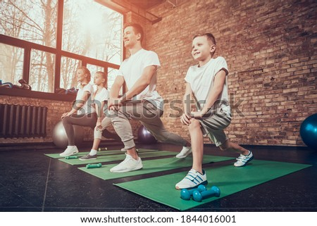 Young family in gym doing exercises and smiling. A boy stands on a mat in shoes and does muscle stretching exercises.  Stock photo ©