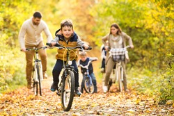 Young family in warm clothes cycling in autumn park