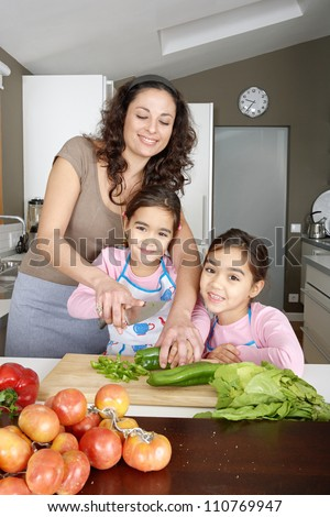Young family kids learning to chop vegetables in the kitchen with mum, smiling.