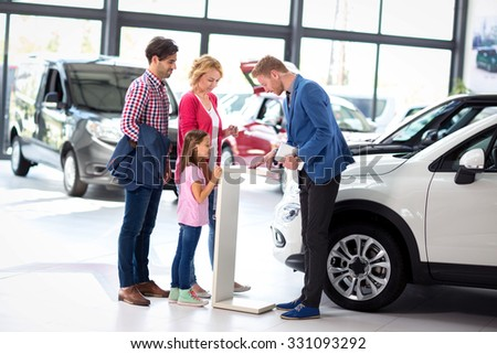 Young  family listens carefully car dealers while their polite salesman presents an offer