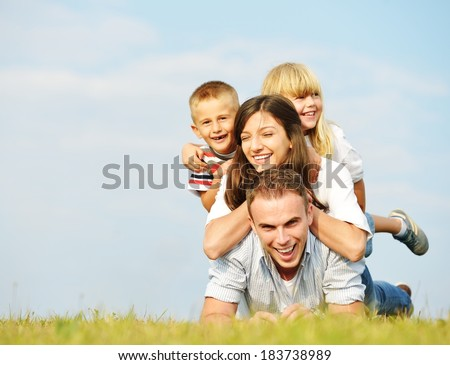 Young family lying on green summer grass meadow having happy life