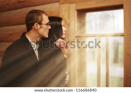 young family man and a woman in a rustic wooden house