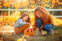 Young family mother and daughter standing at garden outdoors preparing for halloween playing with carved pumpkin laughing happy