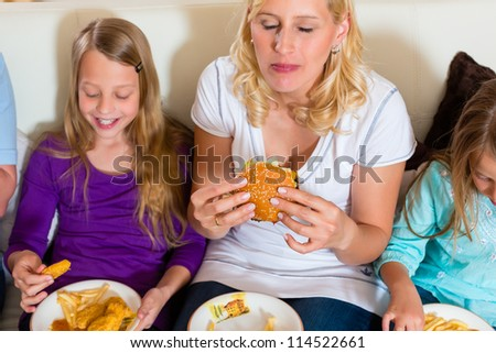 Young family - mother and daughters - is eating hamburger or fast food at home
