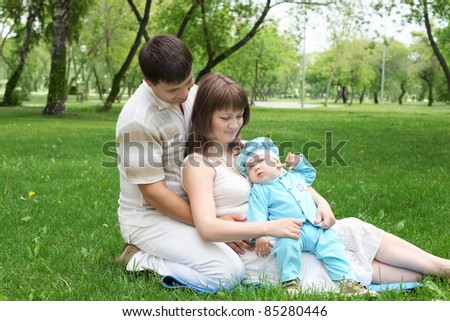 Young family of mother, father and baby son together in the park