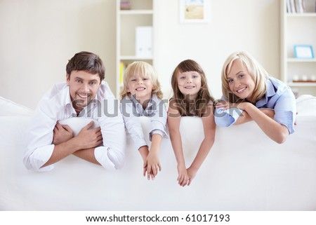 Young family on a white sofa - stock photo