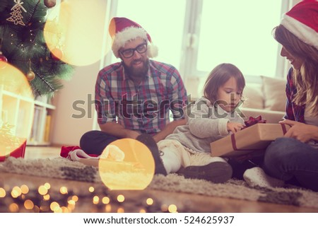 Young family on Christmas morning exchanging presents and enjoying their time together. Focus on the baby girl