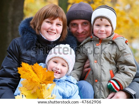 Young family (parents with small children) in golden autumn city park