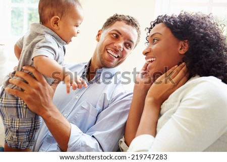 Young Family Playing With Happy Baby Son At Home