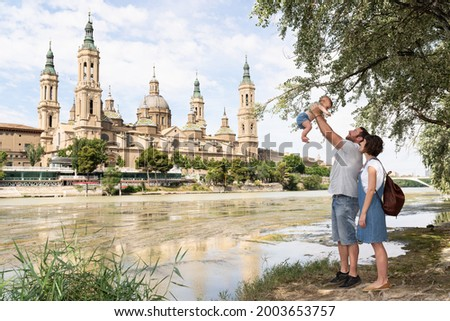 Young family playing with their baby at the Ebro river bank with Basilica del Pilar on the background. Family vacation in Zaragoza, Spain. Foto stock ©