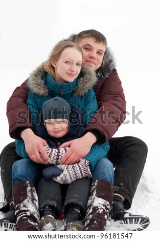 Young family rides to the hills on sleds - stock photo
