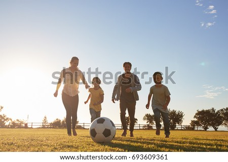 Young family running after a football in a park - Shutterstock ID 693609361