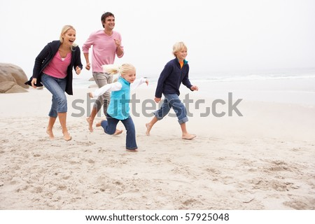 Young Family Running Along Winter Beach