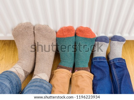 Young family's feet warming cold feet in front of heating radiator. Gas boiler or electric heater at home.