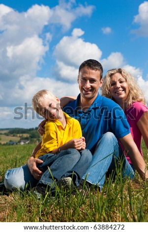 Young family sitting in the sun on the meadow an a bright summer day